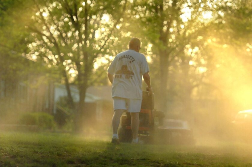 FILE - In a Monday, April 5, 2010, file photo, Shane Nantz kicks up a cloud of pollen as he mows the front yard of his west Charlotte, N.C., home. Seasonal allergy sufferers can try newly FDA-approved types of immnotherapy, once-a-day tablets containing freeze-dried grass extract that dissolve quickly under the tongue, steadily lessening the excessive immune reaction much like the shots. (AP Photo/The Charlotte Observer, Todd Sumlin, File)