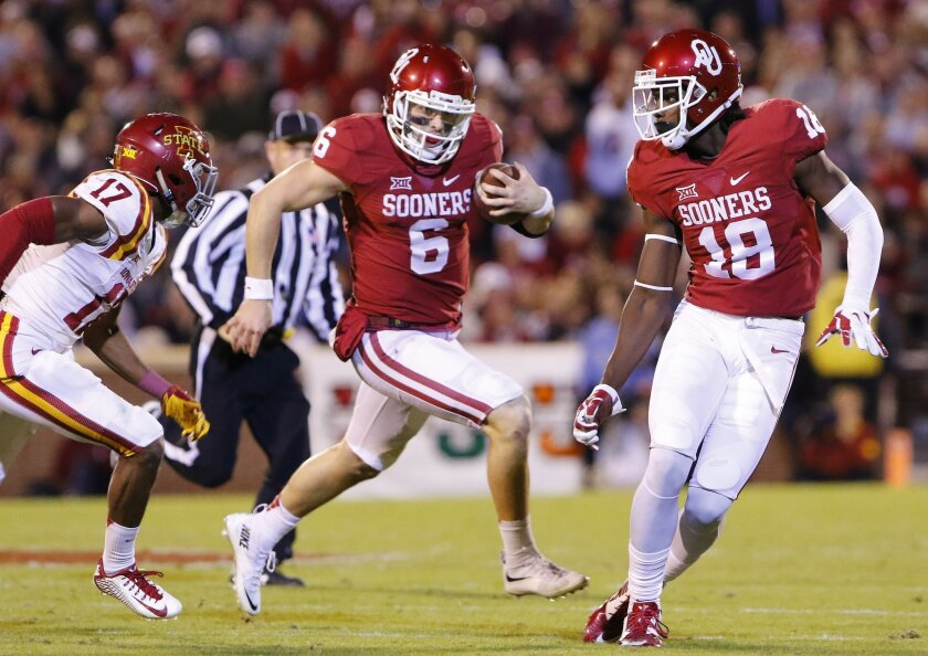 Oklahoma quarterback Baker Mayfield (6) runs ahead of Iowa State defensive back Jomal Wiltz (17) as Oklahoma wide receiver Dahu Green (18) looks to block during the third quarter of an NCAA college football game in Norman, Okla., on Saturday, Nov. 7, 2015. Oklahoma won 52-16. (AP Photo/Alonzo Adams