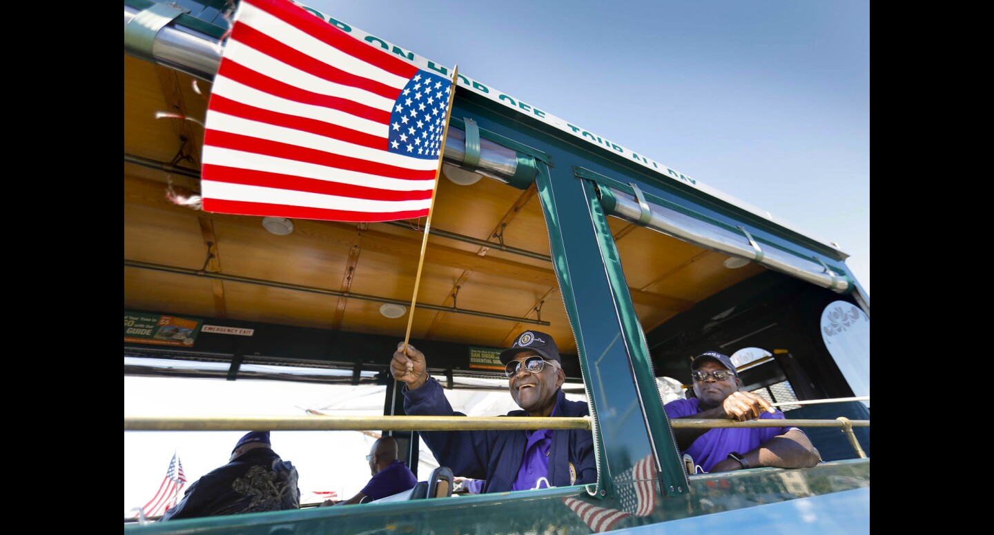 Marine Corps veteran Boyd Linwood waves an American flag while riding in the 32nd annual Veterans Day Parade as it made its way along North Harbor Drive.
