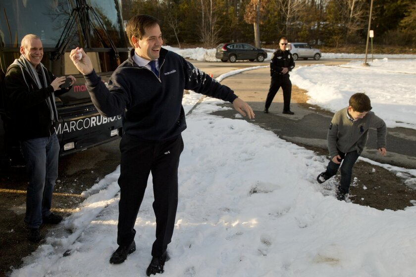 Republican presidential candidate, Sen. Marco Rubio, R-Fla., holds a snow ball and does not throw while playing with his children after a campaign stop Sunday, Feb. 7, 2016, in Hudson, N.H. (AP Photo/Matt Rourke)