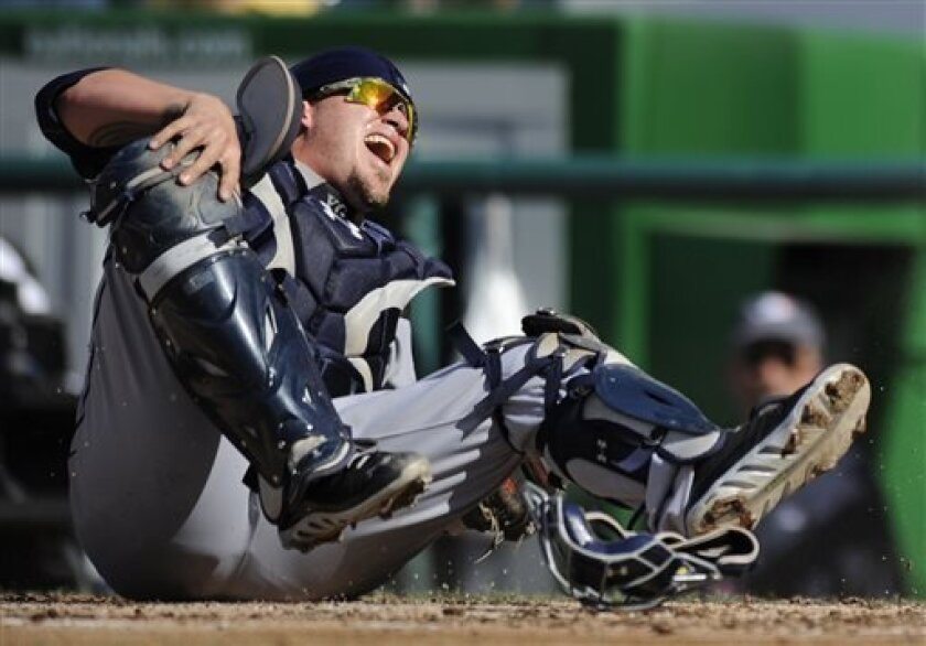 San Diego Padres catcher Yasmani Grandal reacts after he was wiped out on a play at home plate Saturday, sustaining a knee injury that put him on the 60-day disabled list Sunday. (AP Photo/Nick Wass)