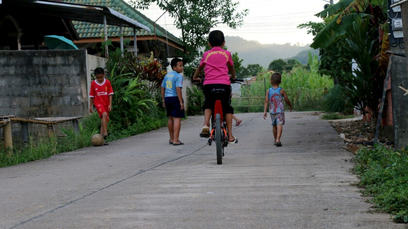 Children play outside the home of 16-year-old Pornchai Khamluang, who goes by the nickname Tee. He w