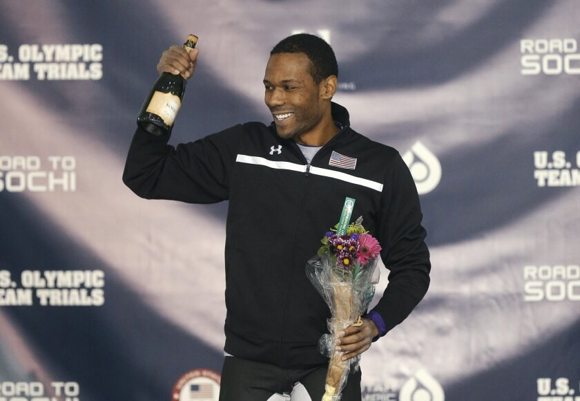 Shani Davis celebrates smiles on the podium after winning the men's 1,500 meters during the U.S. Olympic speedskating trials Tuesday, Dec. 31, 2013, in Kearns, Utah. (AP Photo/Rick Bowmer)