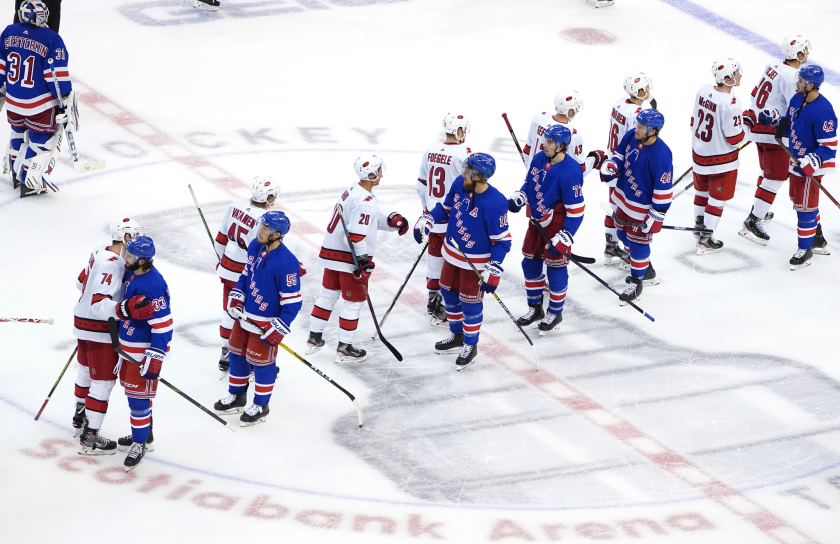 Members of the Carolina Hurricanes and New York Rangers bump gloves at the conclusion of a playoff qualifying series.