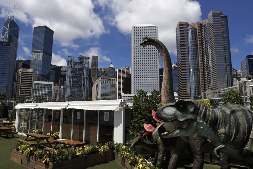 Dinosaur statues are displayed at the Central, a business district in Hong Kong, Saturday, June 20, 2020. China's top legislative body has taken up a draft national security law for Hong Kong that has been strongly criticized as undermining the semi-autonomous territory's legal and political institutions. (AP Photo/Kin Cheung)