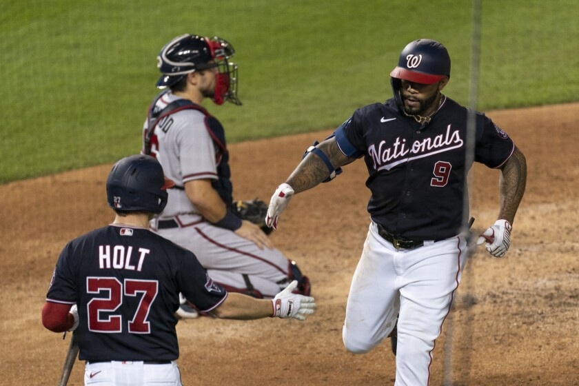 Washington Nationals' Eric Thames (9) is congratulated by Brock Holt (27) after hitting a home run during the fifth inning of the team's baseball game against the Atlanta Braves in Washington, Friday, Sept. 11, 2020. (AP Photo/Manuel Balce Ceneta)