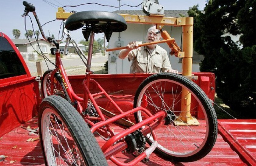 Doug Qua used a lift to unload his tricycle at his home Thursday. 