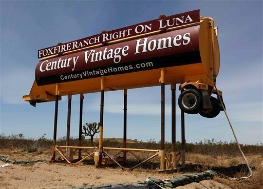 A partially demolished sign advertising a housing development is shown Tuesday May 5, 2009 in Victorville, Calif. The homes, part of a planned 16-unit project, fell victim to the housing price crash and developers decided it would be easier to demolish the houses than complete and sell them. (AP Photo/Nick Ut)