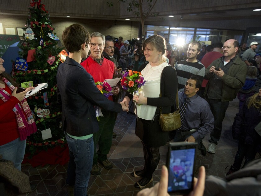 Natalie Dicou, left, and Nicole Christensen are married by Salt Lake City Mayor Ralph Becker in the lobby of the Salt Lake County Clerk's Office in Salt Lake City.