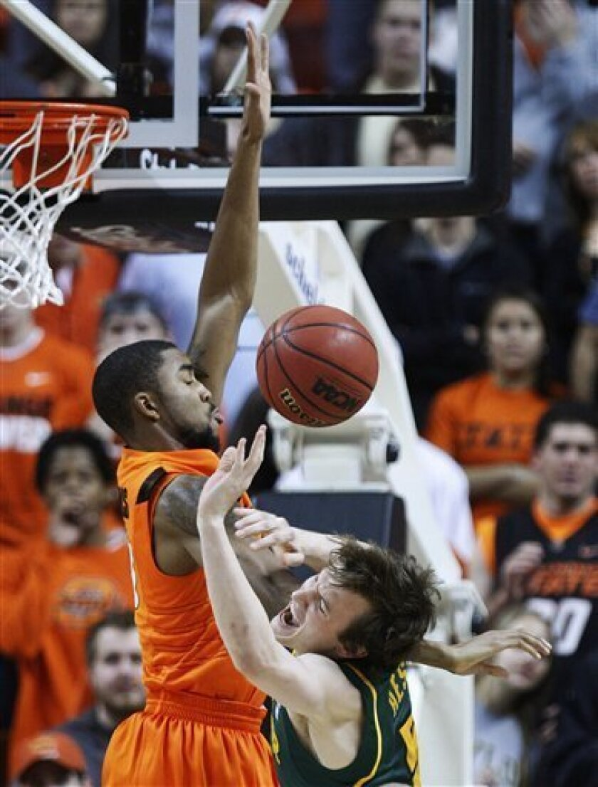 Oklahoma State forward Mike Cobbins, left, and Baylor guard Brady Heslip, right, collide as Heslip goes up for a shot in the first half of an NCAA college basketball game in Stillwater, Okla., Saturday, Feb. 4, 2012. (AP Photo/Sue Ogrocki)