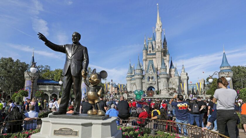 FILE - In this Jan. 9, 2019 photo, guests watch a show near a statue of Walt Disney and Micky Mouse