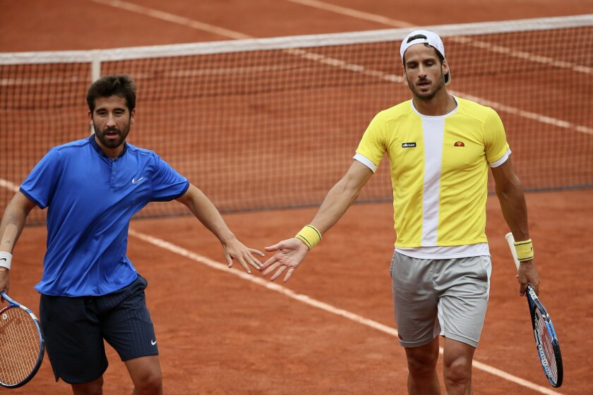 Spanish pair Feliciano Lopez, right, and Marc Lopez congratulate each other as they play Bob Bryan and Mike Bryan, of the U.S, during their men's doubles final match of the French Open tennis tournament at the Roland Garros stadium, Saturday, June 4, 2016 in Paris.  (AP Photo/David Vincent)