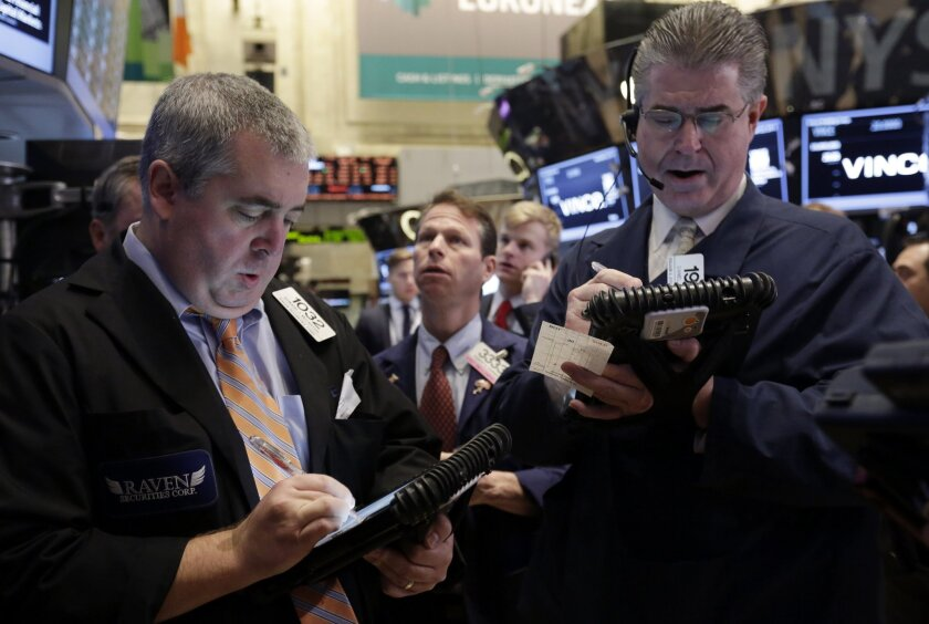 FILE - In this Friday, Nov. 22, 2013, file photo, traders work on the floor of the New York Stock Exchange. (AP Photo/Richard Drew, File)