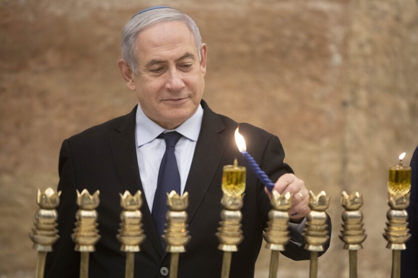 Israeli Prime Minister Benjamin Netanyahu lights a Hanukkah candle at the Western Wall in Jerusalem's Old City on Dec. 22.