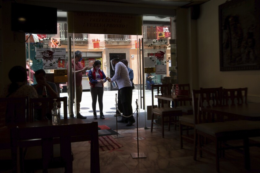 A waiter hands out disinfectant to customers before entering a Chinese restaurant in downtown Mexico City, Friday, July 3, 2020. Limited reopening of restaurants and other businesses in the capital this week came as new coronavirus cases continued to climb steadily. (AP Photo/Fernando Llano)