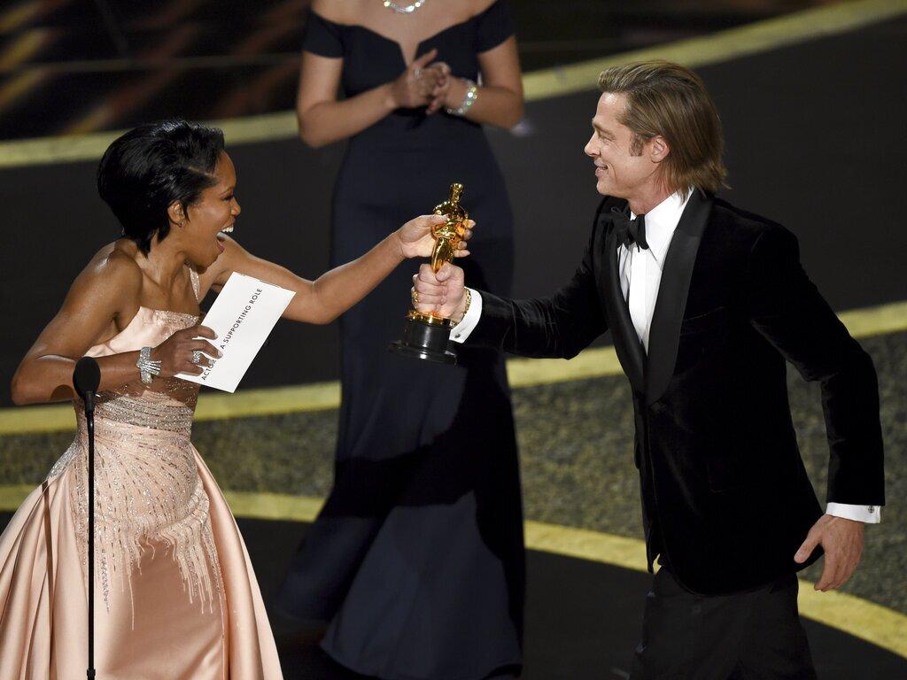 """Regina King, izquierda, entrega a Brad Pitt el premio a mejor actor de reparto por """"Once Upon a Time in Hollywood"""" en los Oscar el domingo 9 de febrero de 2020 en el Teatro Dolby, en Los Angeles. (Foto AP/Chris Pizzello)"""