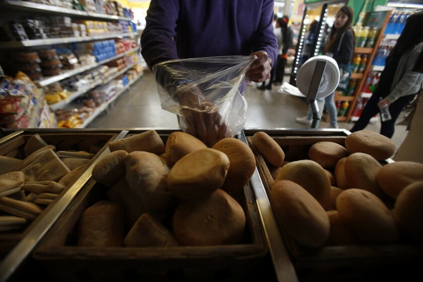 In this Sept. 3, 2015, photo, a man buys bread at a Wal-Mart Ekono convenience store in Santiago, Chile. Chile is one of the world's top three bread-consuming countries, along with Germany and Switzerland. (AP Photo/Luis Hidalgo)