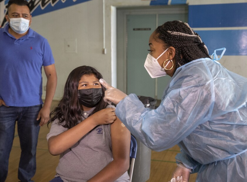A girl rolls up a sleeve as a person in a face mask and body covering points a finger.