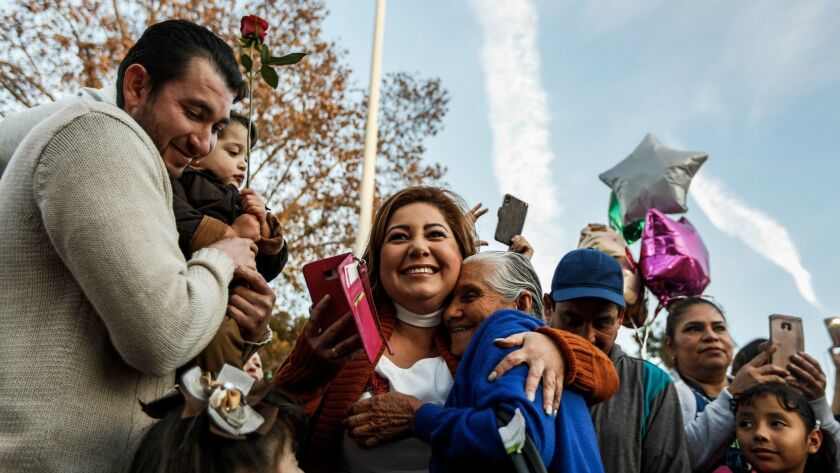 Maria Flores Alvarado, center, hugs her mother-in-law, Salud Fernandez, at Spane Park in Paramount just after Fernandez arrived from Michoacan, Mexico.