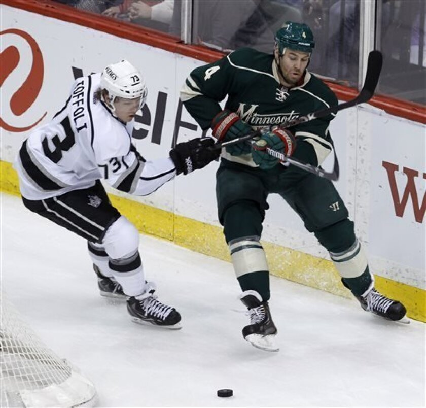 Los Angeles Kings center Tyler Toffoli (73) holds Minnesota Wild defenseman Clayton Stoner (4) back from the puck during the first period of an NHL hockey game in St. Paul, Minn., Saturday, March 30, 2013. (AP Photo/Ann Heisenfelt)