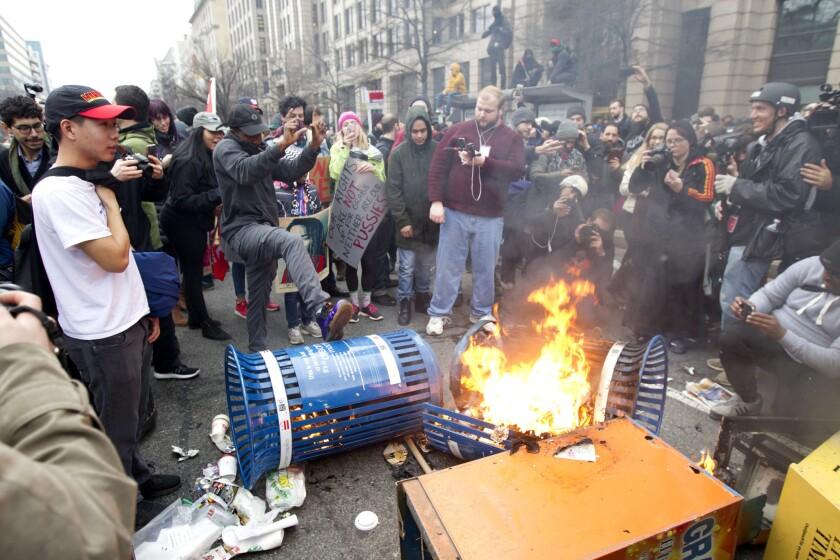 Manifestantes queman botes de basura durante una protesta en el centro de Washington el viernes 20 de enero de 2017, durante la ceremonia de investidura del presidente Donald Trump. (AP Foto/Jose Luis Magana)