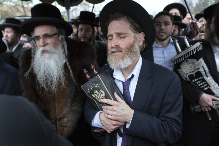 Rabbi Chaim Rottenberg, left, and others celebrate the arrival of a new Torah on Sunday. A day earlier, multiple people were stabbed in his home.