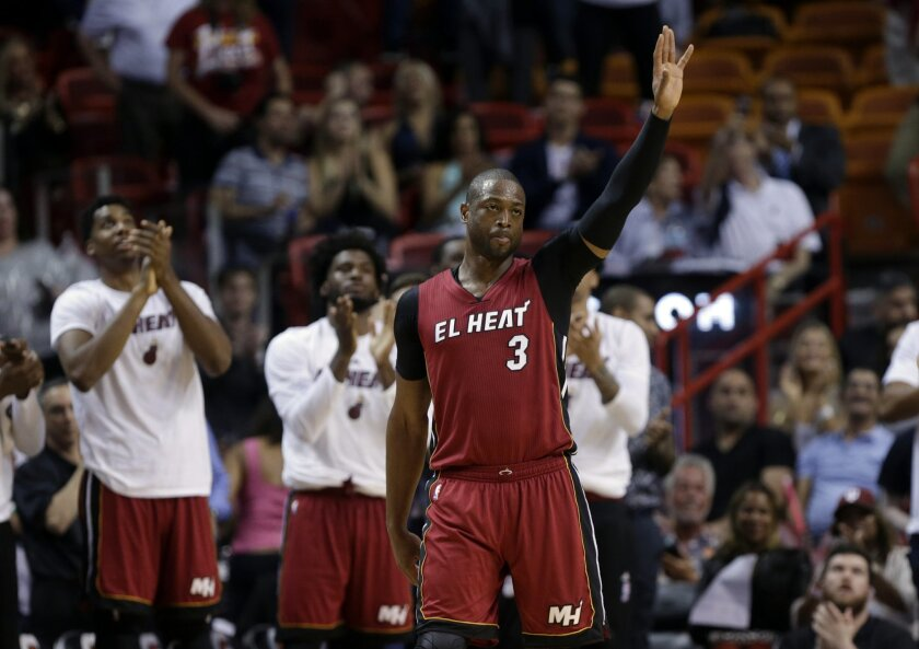 Miami Heat guard Dwyane Wade (3) waves to the crowd after being acknowledged for scoring 20,000 career points during the second half of an NBA basketball game against the Cleveland Cavaliers, Saturday, March 19, 2016, in Miami. (AP Photo/Lynne Sladky)