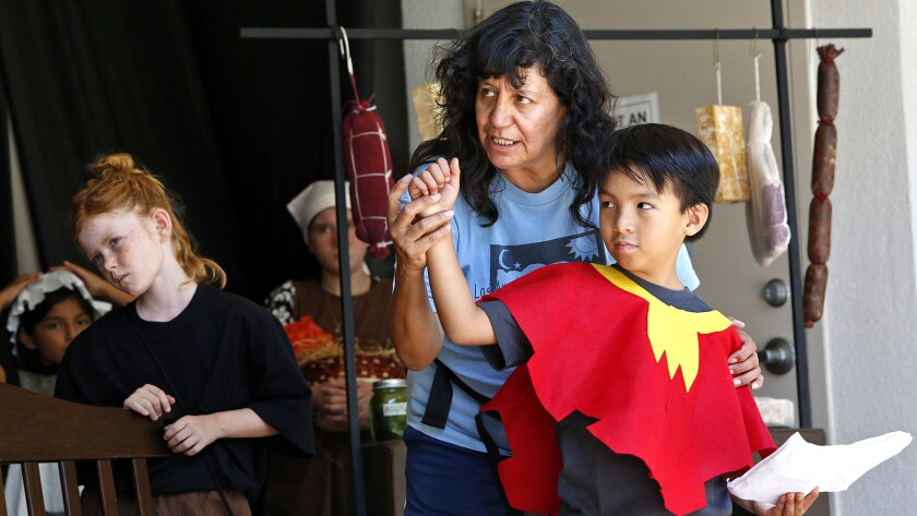 Alejandra Flores, center, gives directions in Spanish to Camilo Choi, right, as Stella Ferguson, left, listens during a one-week Spanish-only theater camp at Elysian Park.