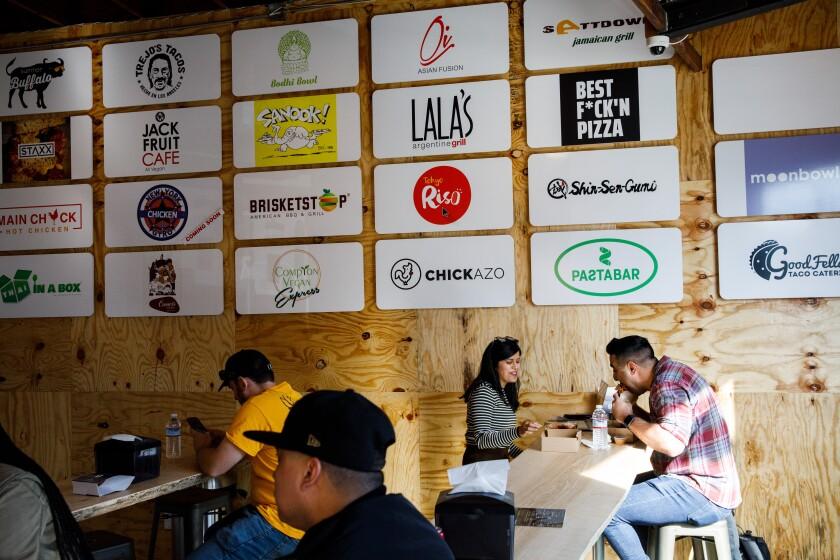 UCLA students Radhika Sakalkale and Bobby Bastin, right, eat Main Chick Hot Chicken sandwiches at Colony.
