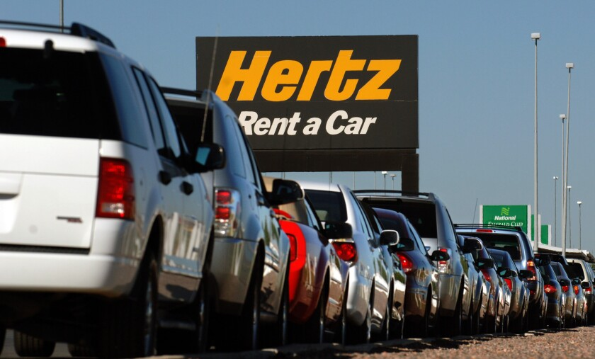 A row of rental cars are parked below a Hertz Corp. sign
