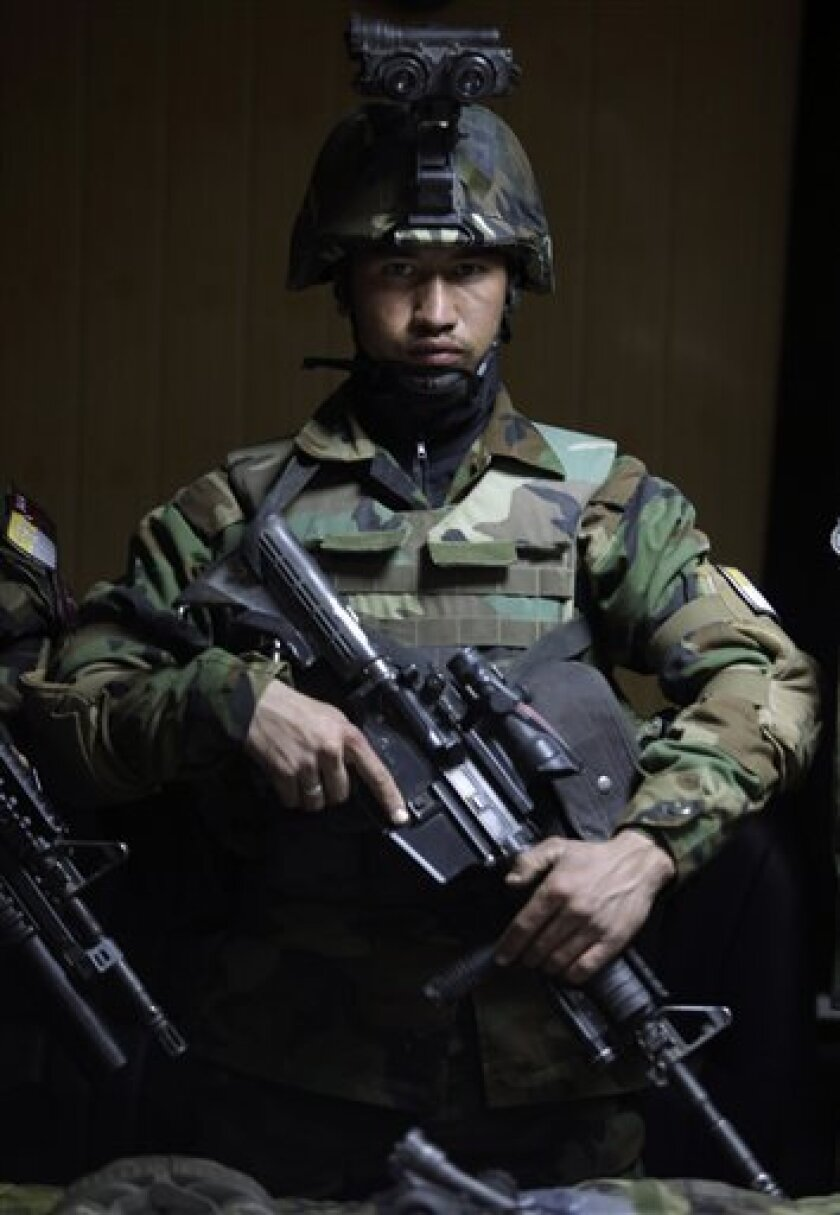 An Afghan Army commando stands in front of weapons on display for the media, in Kabul, Afghanistan, Wednesday, Jan. 5, 2011. (AP Photo/Altaf Qadri)