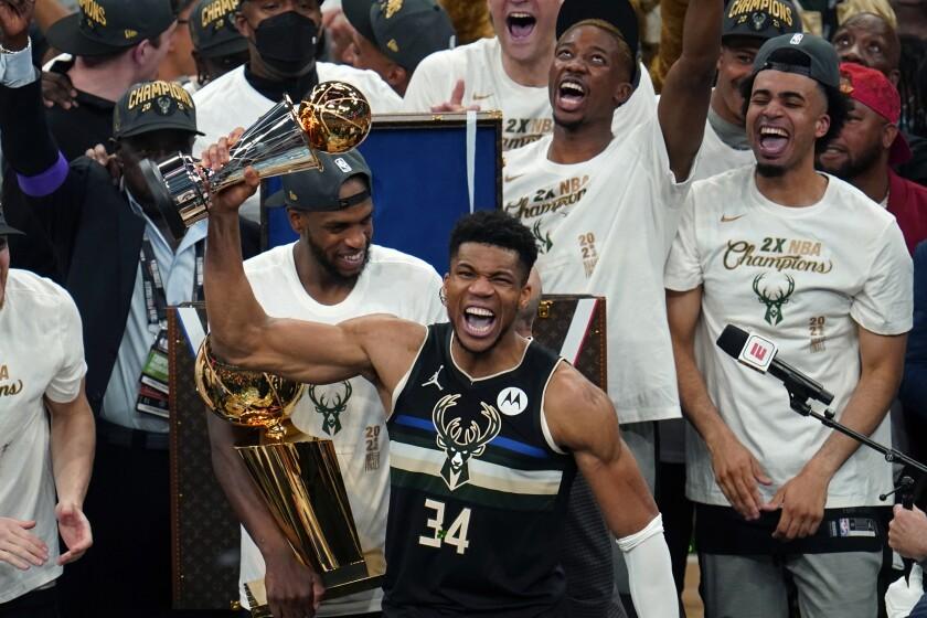 Milwaukee Bucks forward Giannis Antetokounmpo reacts with the championship trophy.