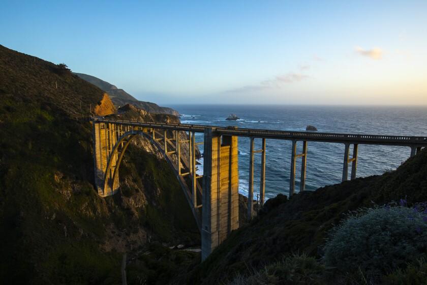 The setting sun falls on an old bridge near ocean cliffs.