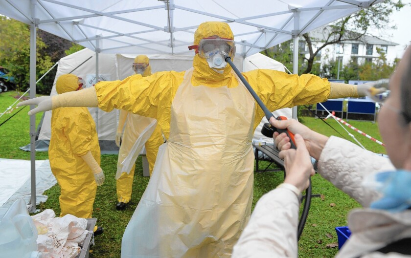 A doctor who has volunteered to travel to West Africa to help care for Ebola patients is disinfected during training offered by the German Red Cross in Wuerzburg.