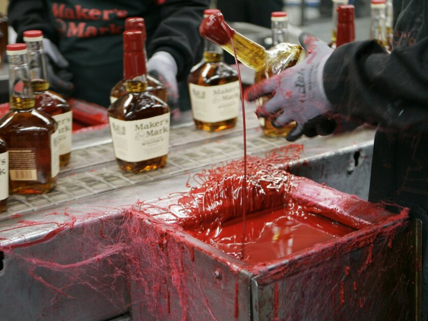 FILE - In this Wednesday, April 8, 2009, file photo, a bottle of Maker's Mark bourbon is dipped in red wax during a tour of the distillery in Loretto, Ky. Kentucky bourbon makers have stashed away their largest stockpiles in more than a generation due to resurgent demand for the venerable brown spi