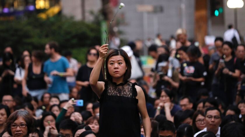 A woman holds a flower as she joins hundreds of mothers protesting against the amendments to the ext