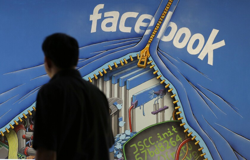 """A man walks by a mural at the Facebook campus in Menlo Park, Calif. Facebook is planning to release a toolset called """"Facebook at Work"""" that would allow users to communicate with their co-workers using the social network's traditional tools, such as news feed, messaging and groups."""
