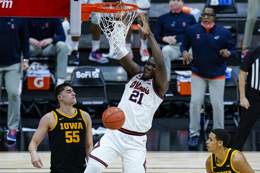 Illinois center Kofi Cockburn (21) gets a dunk over Iowa center Luka Garza (55) in the second half of an NCAA college basketball game at the Big Ten Conference tournament in Indianapolis, Saturday, March 13, 2021. Illinois defeated Iowa 82-71. (AP Photo/Michael Conroy)