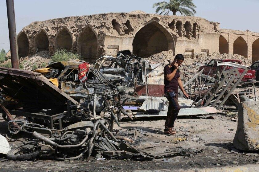 Un civil inspecciona el lugar donde el viernes or la noche se produjo un ataque suicida en un mercado en Jan Beni Saad, 30 kilómetros al noreste de Bagdad, sábado 18 de julio de 2015. El ataque dejó 115 muertos.
