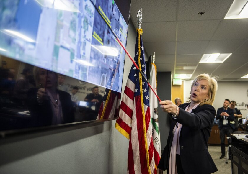District Attorney Anne Marie Schubert uses a pointer to point to a spot on a satellite map on a TV screen