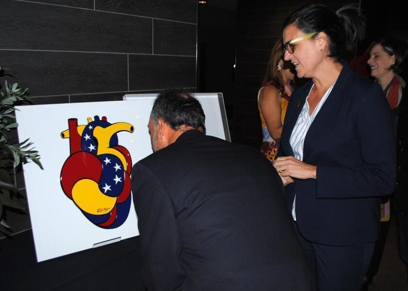 """La artista venezolana Rayma Suprani (d) enseña su obra que simboliza un corazón con los colores de la bandera de Venezuela este jueves, durante un evento en Miami (EE.UU.). La Fundación Más is More entregó este jueves un """"Corazón Venezuela"""", obra de Suprani, a la vicepresidenta de Perú, Mercedes Aráoz, por su """"generosa participación en conseguir las vías para la libertad y democracia de Venezuela"""". EFE"""