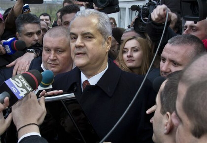Former Romanian Premier Adrian Nastase exits the Jilava prison on the outskirts of Bucharest, Romania, after judges voted Monday, March 18, 2013, to allow his immediate release after he served one-third of a two year sentence. His attorney had requested his release on the grounds that he is over ag