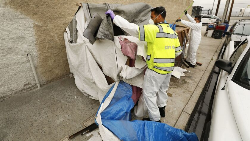Jesus Sanchez, left, and Javier Villarreal of the L.A. Sanitation Bureau clean up a homeless encampment at 41st Place and Alameda Street on May 23.