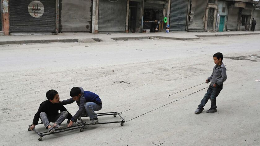 Syrian children play in the once rebel-held Shaar neighborhood in the northern city of Aleppo.