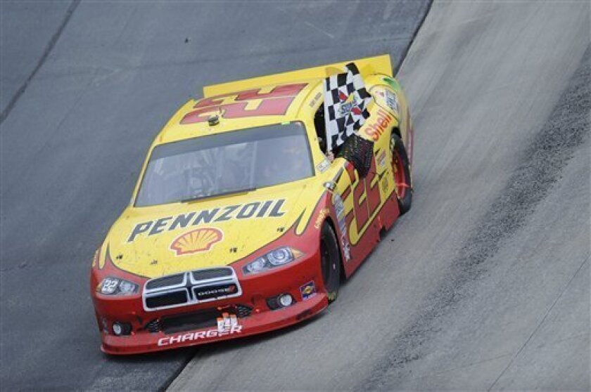 Kurt Busch waves the checkered flag from his car on a victory lap after he won the NASCAR Sprint Cup Series auto race at Dover International Speedway in Dover, Del., Sunday, Oct. 2, 2011. (AP Photo/Nick Wass)