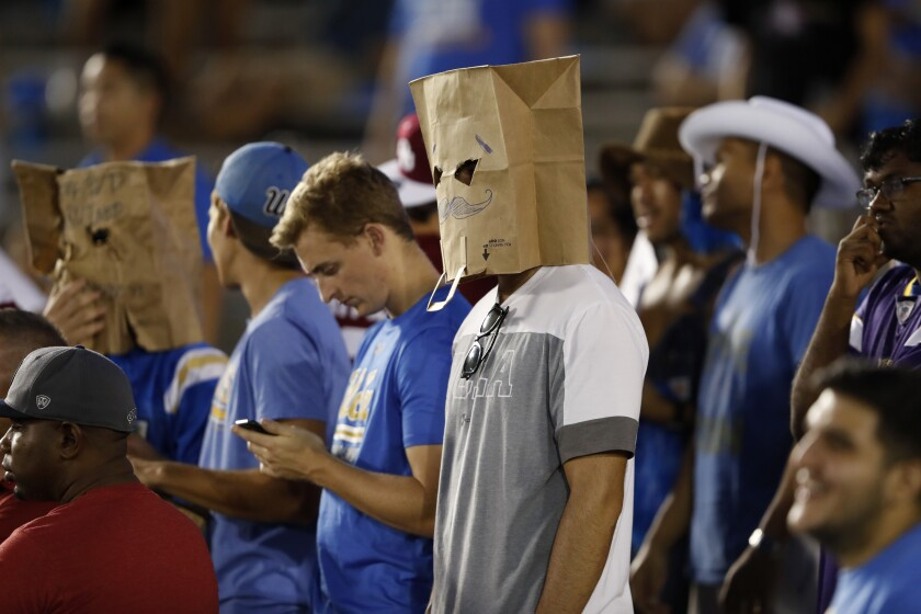 UCLA fans wear paper bags over their heads.