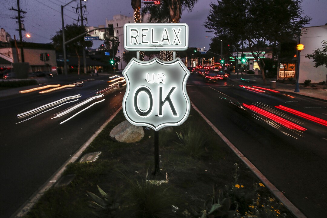 A neon sign in the shape of a highway shield on a median says Relax you're OK