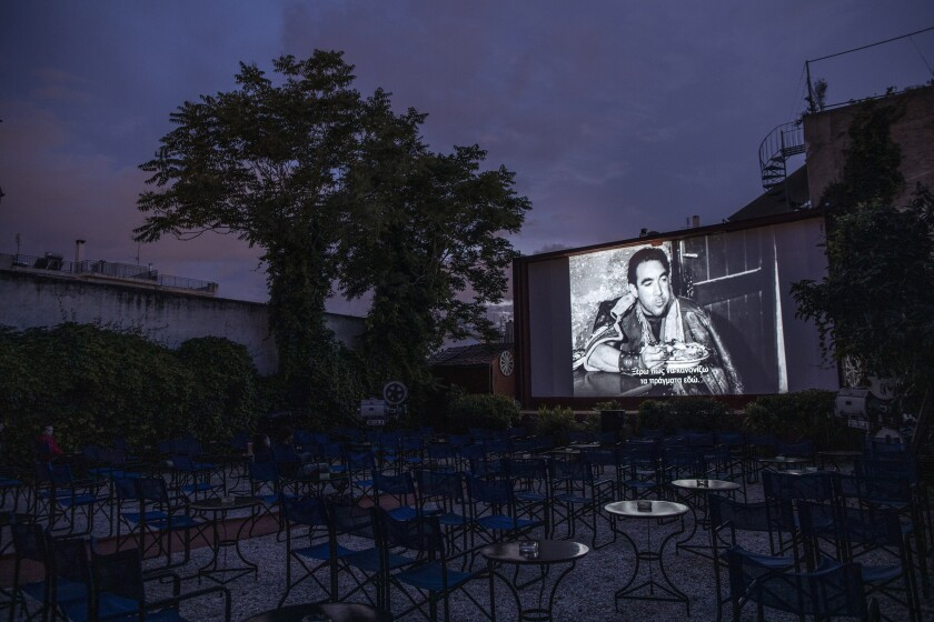 In this Monday June 1, 2020 photo, actor Anthony Quinn is shown on the screen in La Strada, a 1954 Italian drama film directed by Federico Fellini at the Zephyros open-air cinema that specializes in films from past decades in Athens' central Petralona district, on the first day it opened after the easing of Greece's coronavirus lockdown. (AP Photo/Petros Giannakouris)