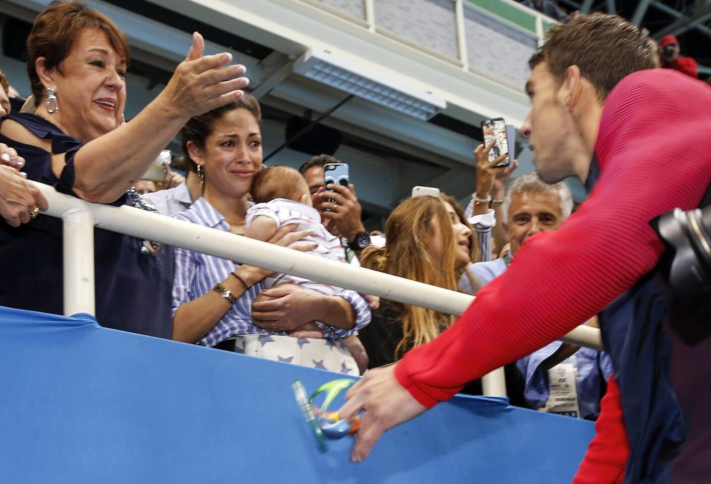 Michael Phelps of USA (R) goes to see his mother Deborah (L), his fiancee Nicole Johnson (C) and their son Boomer during the round of honour after the medal ceremony for the men's 200m Butterfly final race of the Rio 2016 Olympic Games Swimming events at Olympic Aquatics Stadium at the Olympic Park in Rio de Janeiro, Brazil.