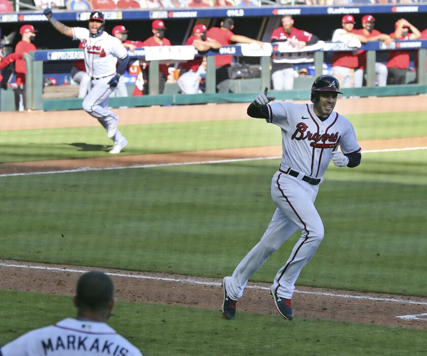 Atlanta Braves' Cristian Pache, rear left, heads home to score the winning run as Braves' Freddie Freeman celebrates heading to first after hitting an RBI single to beat the Reds 1-0 in 13 innings in Game 1 of a National League wild-card baseball series, Wednesday, Sept. 30, 2020, in Atlanta. (Curtis Compton/Atlanta Journal-Constitution via AP)